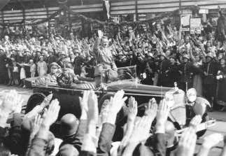 A photograph of Adolf Hitler parading in a parade waving to the crowds.