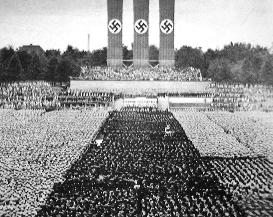 A photograph of throngs of people standing beneath three giant swastikas.